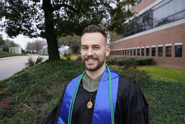 Chris Foley, BS in Healthcare Studies 2019 standing outside in his regalia.