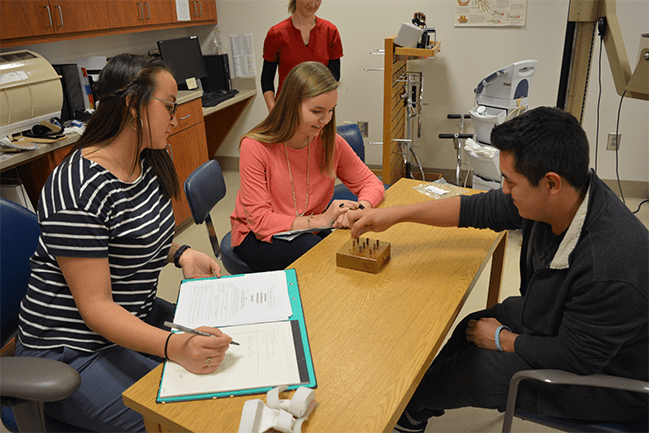 Occupational therapy student helping a patient while a supervisor looks on.