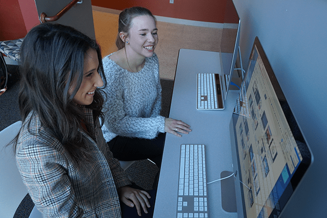 Two occupational therapy students sitting in front of a computer
