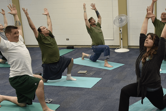 OT alumnus Kaelyn Rogers practicing yoga with male inmates