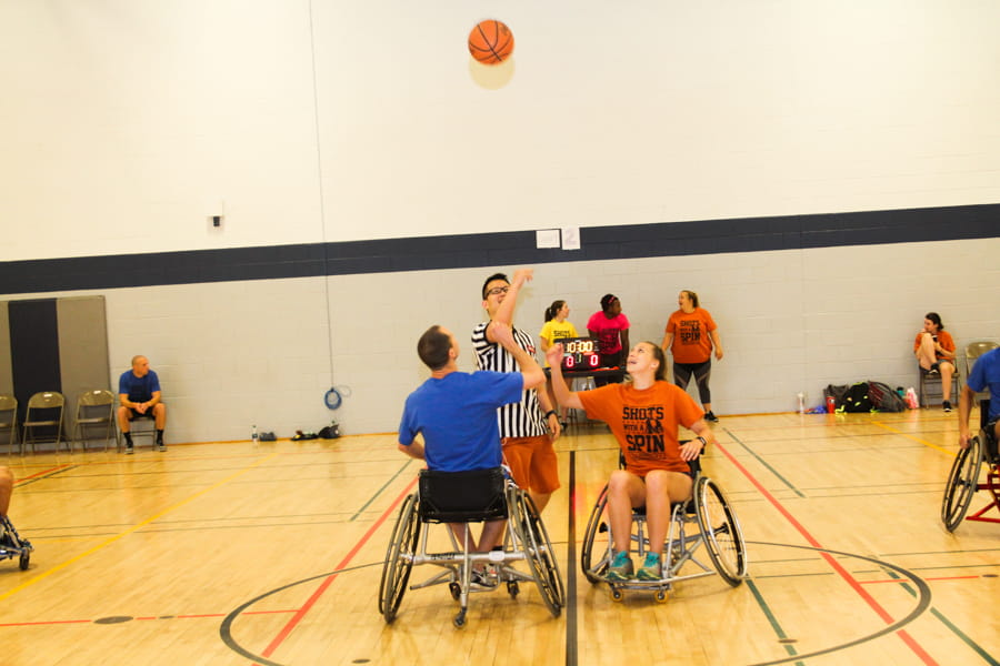 Participants play wheelchair basketball at the Shots with a Spin tournament.
