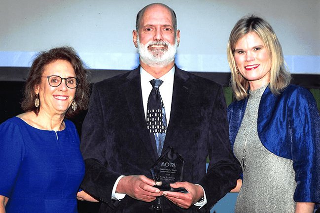 Dr. Craig Velozo accepted his award at the 2019 AOTA Annual Conference. Pictured with (left to right) Ellen Cohn, ScD, OTR/L, FAOTA, 2018 award winner, and AOTA President, Amy Lamb, OTD, OTR/L.