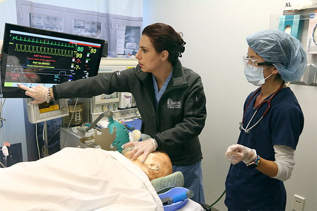 Anesthesia for nurses professor teaching student how to use equipment.