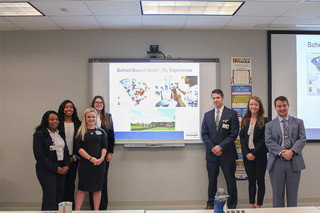 Master of Health Administration students standing in front of a classroom.