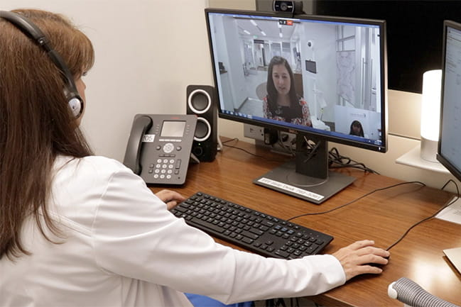 Woman practicing telehealth with a patient.