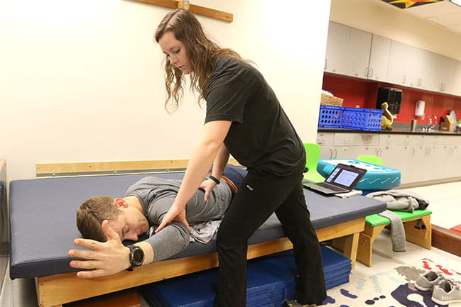 Physical therapy students practicing in a lab class.